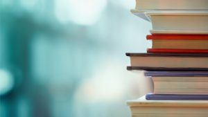 Book,Stack,In,The,Library,Room,And,Blurred,Bookshelf,For